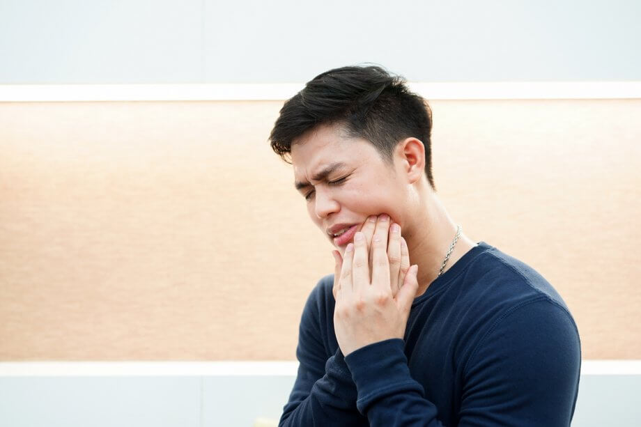 Man Holding Jaw In Pain From Wisdom Tooth Infection